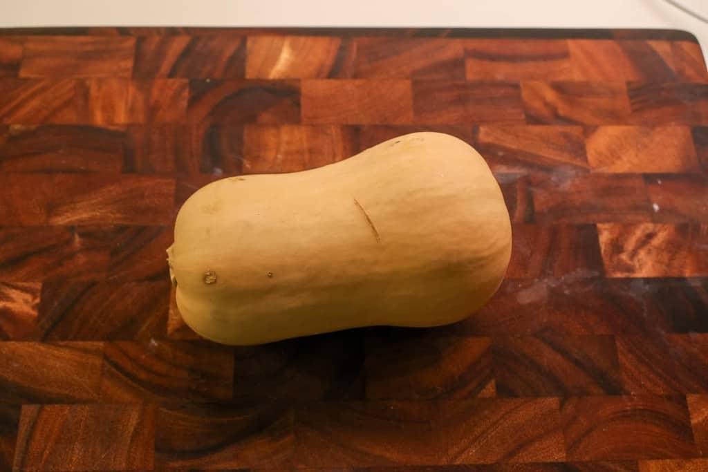 a whole butternut squash on a cutting board