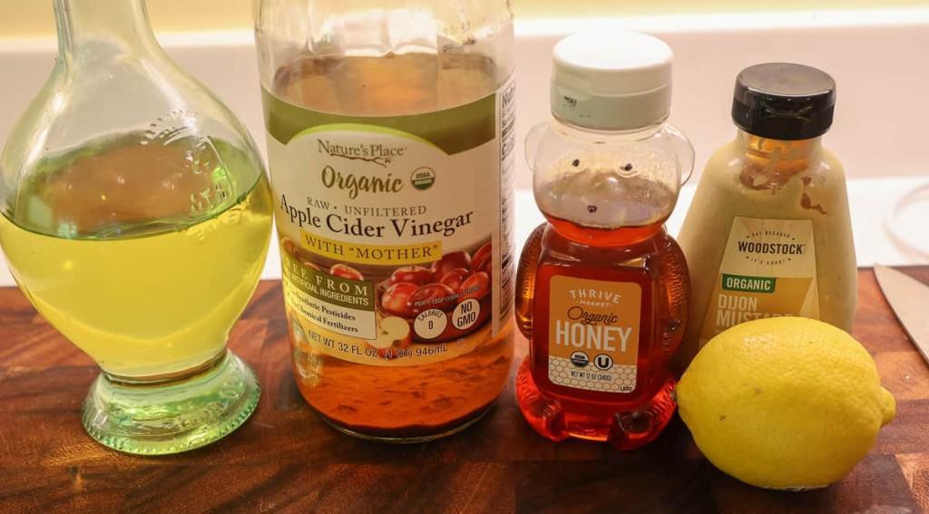 olive oil, apple cider vinegar, honey, dijon and lemon on a cutting board