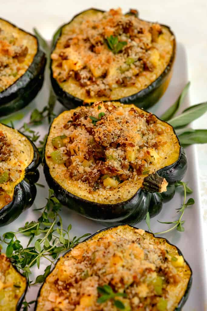 close up of stuffed acorn squash on a white platter surrounded by fresh sage