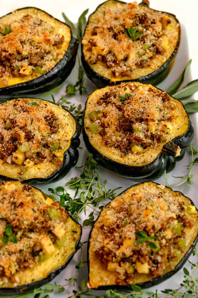 acorn squash cut in half and stuffed with italian sausage, apples, and topped with parmesan panko breadcrumbs. 6 stuffed squash on a white plate