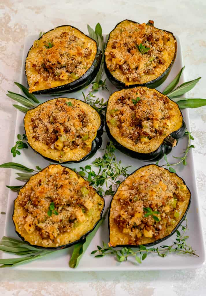 6 stuffed acorn squash on a white platter surrounded by fresh thyme and sage