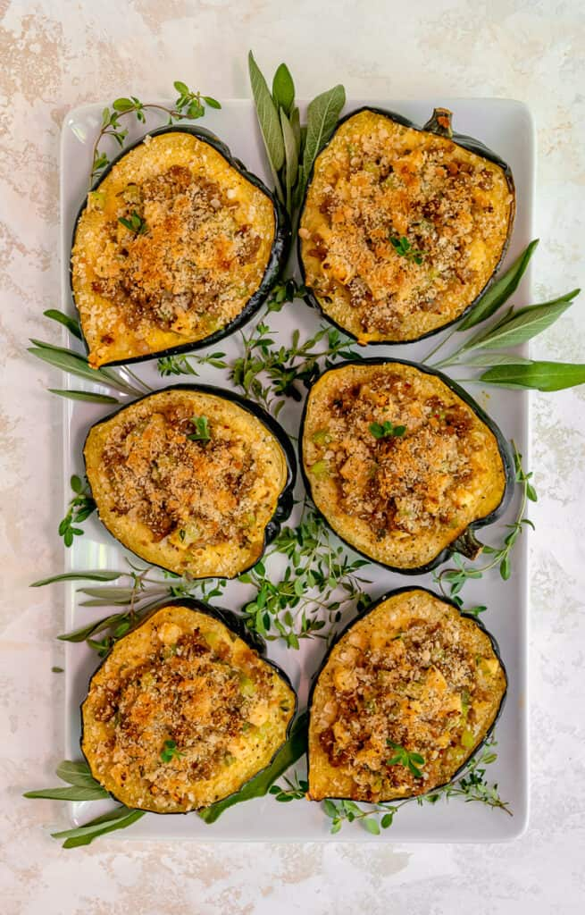 overhead of six stuffed acorn squash surrounded by fresh herbs on a white platter