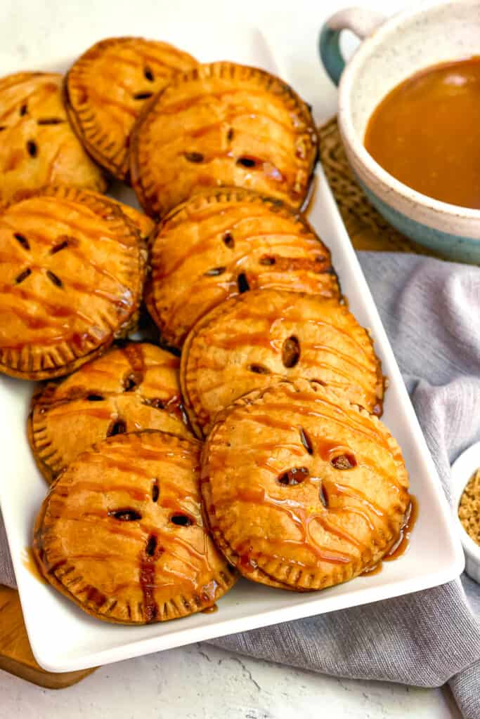 apple pie hand pies on a white plate with caramel drizzle over the top