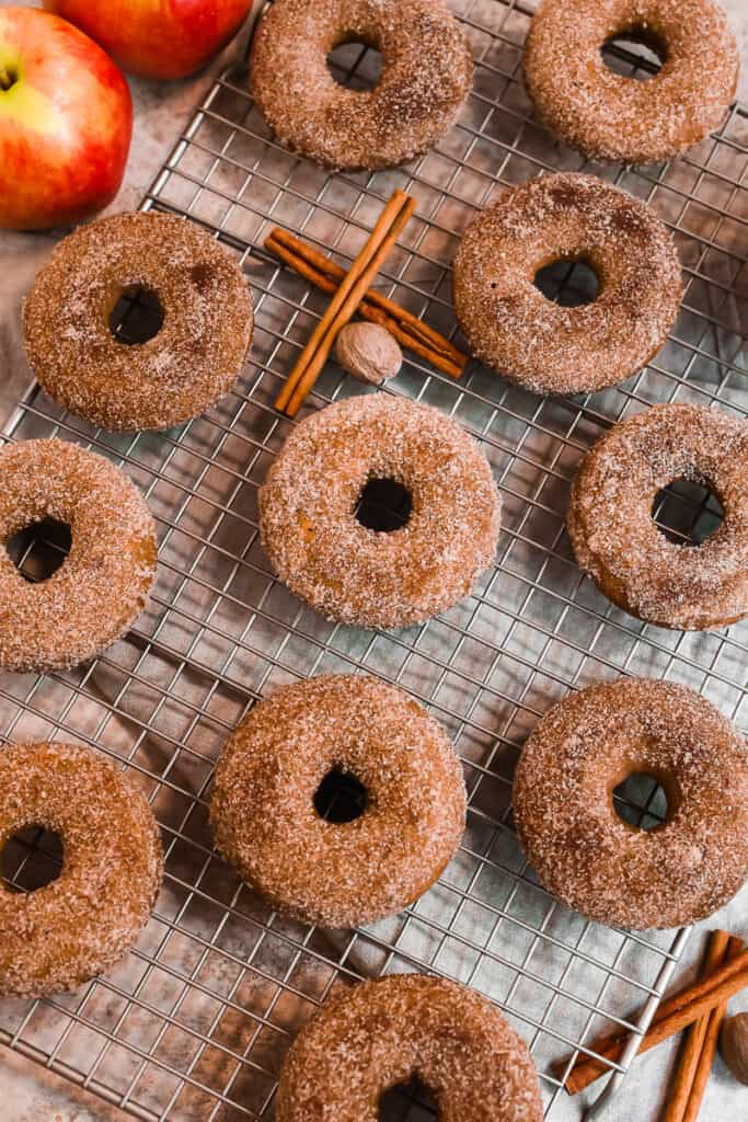 one dozen apple cider donuts on a rack with cinnamon sticks and whole apples