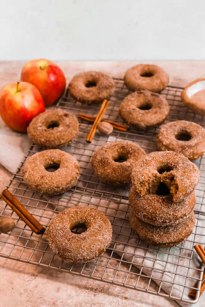 a dozen cinnamon sugar apple cider donuts on a cooling rack surrounded by cinnamon sticks