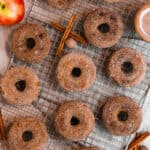 apple cider donuts covered in cinnamon sugar on a cooling rack