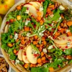 harvest salad in a bowl surrounded by an apple, walnuts, and pomegranate seeds
