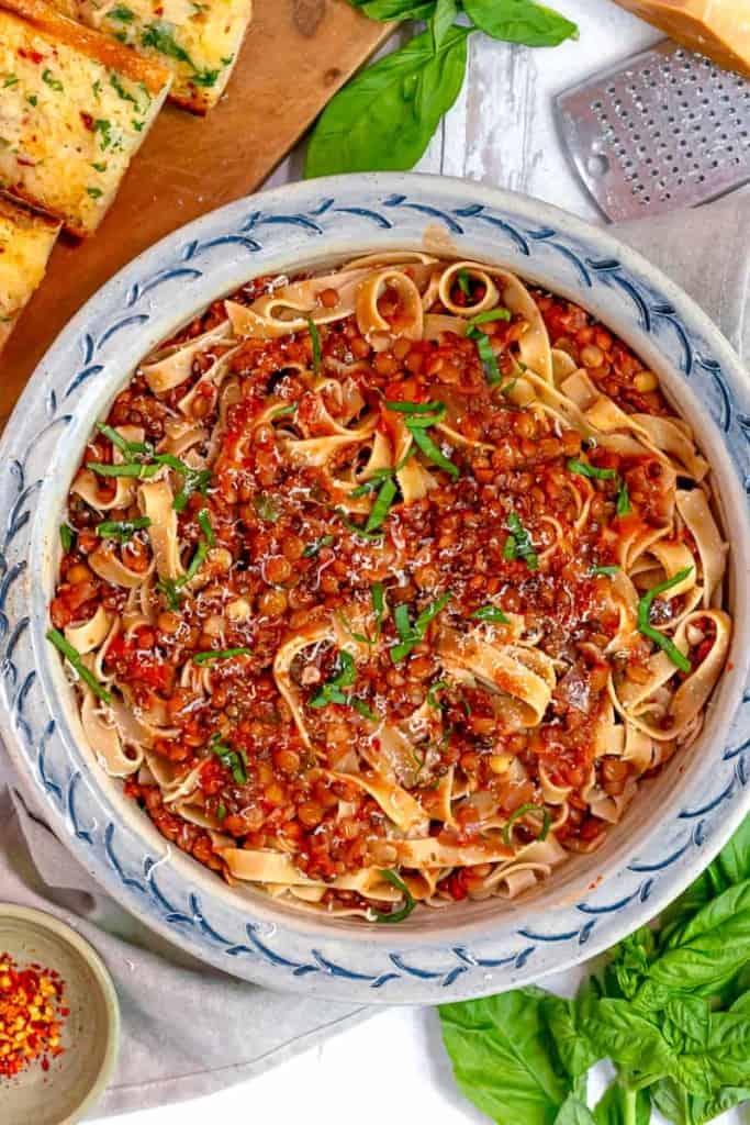 overhead lentil bolognese sauce coating tagliatelle pasta with fresh basil over top