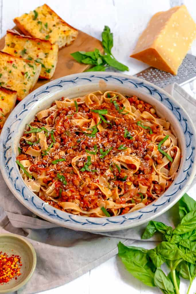 Lentil bolognese over tagliatelle pasta with garlic bread and fresh basil surrounding