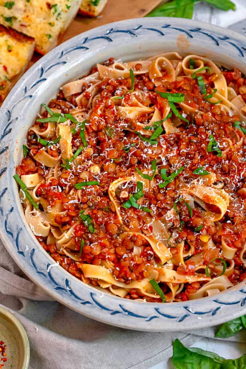 close up of lentil bolognese on top of pasta with garlic bread and fresh basil