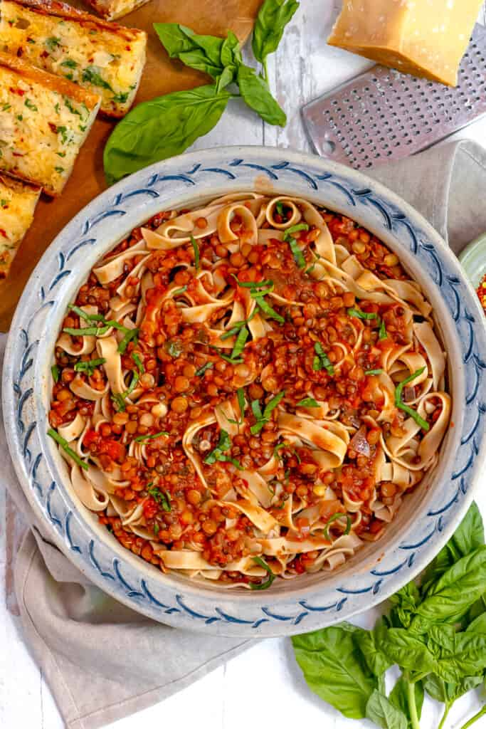 over head photo of lentil bolognese over pasta surrounded by fresh basil