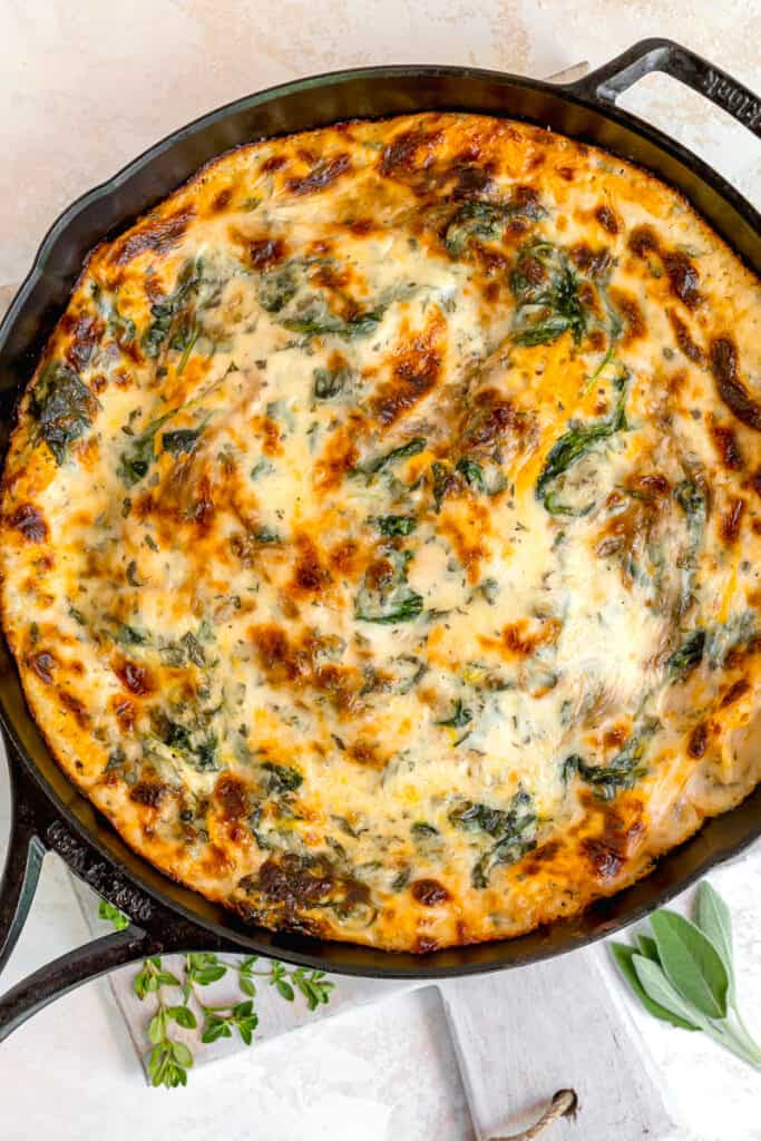 cast iron skillet with squash lasagna, melty cheese, and spinach on top surrounded by fresh thyme and sage