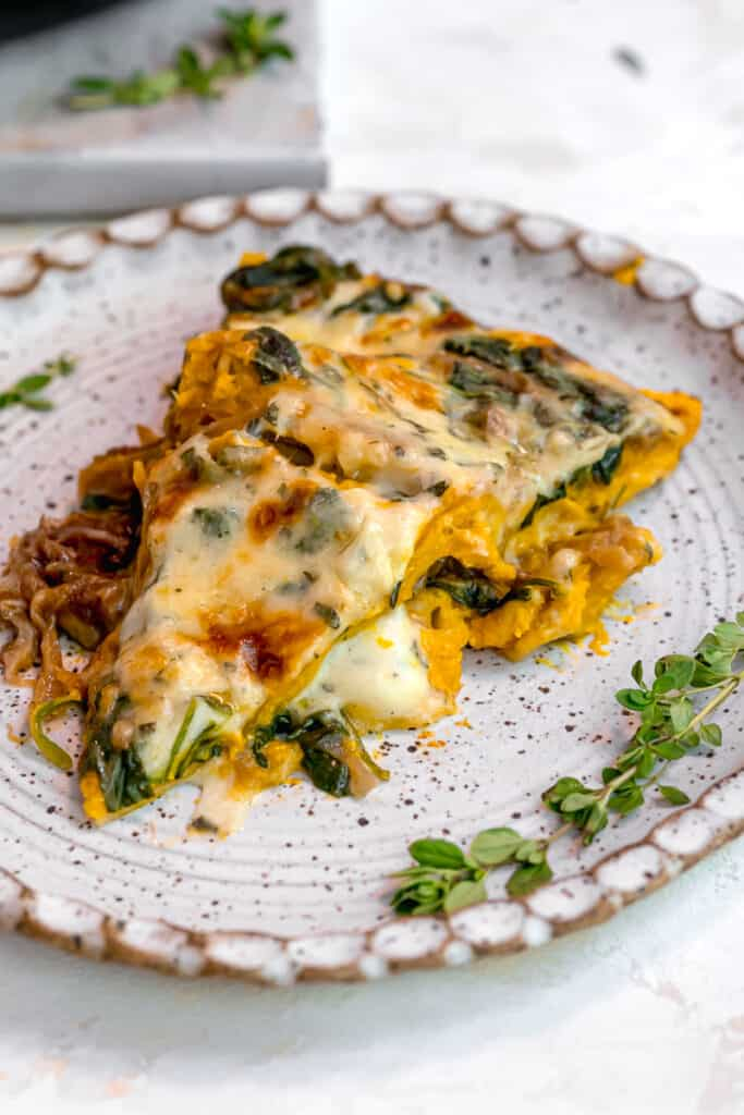 slice of spinach lasagna on white plate surrounded by fresh thyme leaves