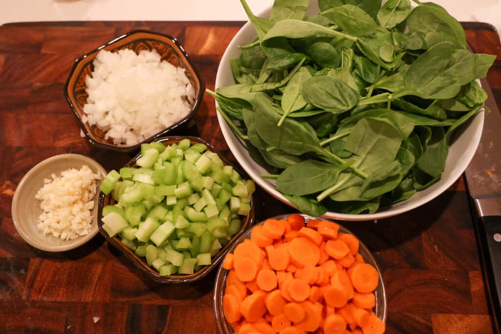 diced celery, onion, garlic, carrots and spinach in bowls