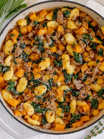 white skillet with gnocchi, butternut squash, kale, and hot italian sausage surrounded by fresh sage and thyme